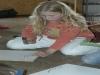 Nele haut die Nägel kreisförmig in eine Holzplatte. Damit sie dann den Kreis schnüren kann.